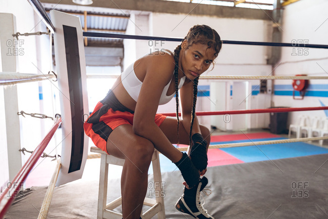 Female boxer looking at camera while relaxing in boxing ring at fitness center