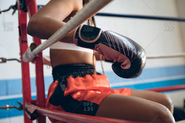Female boxer relaxing in boxing ring at fitness center