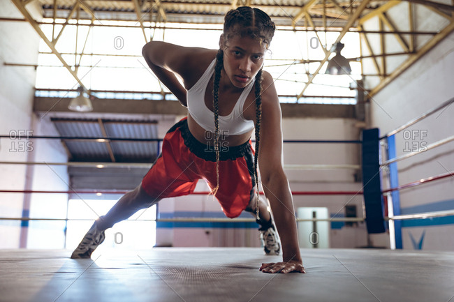 Female boxer looking at camera while exercising in boxing ring