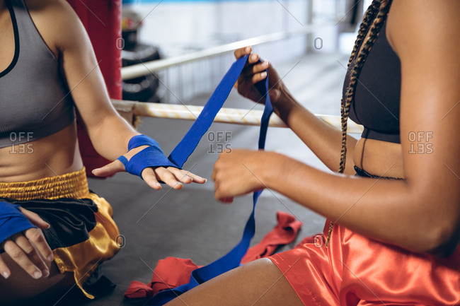 Female trainer putting hand wrap to female boxer in boxing club