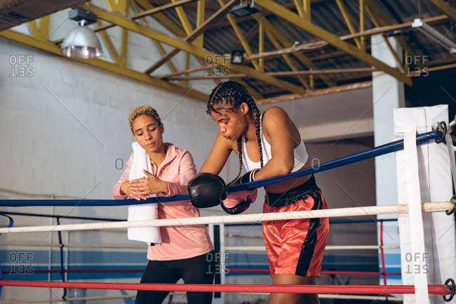 Trainer and female boxer interacting with each other in boxing ring