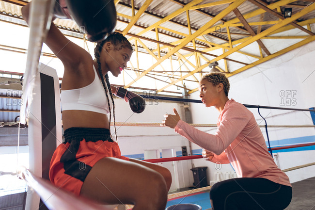Trainer interacting with female boxer in boxing ring