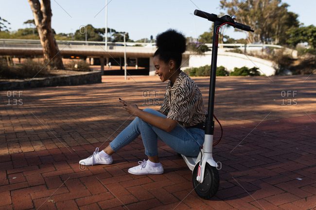 Young woman sitting on e scooter
