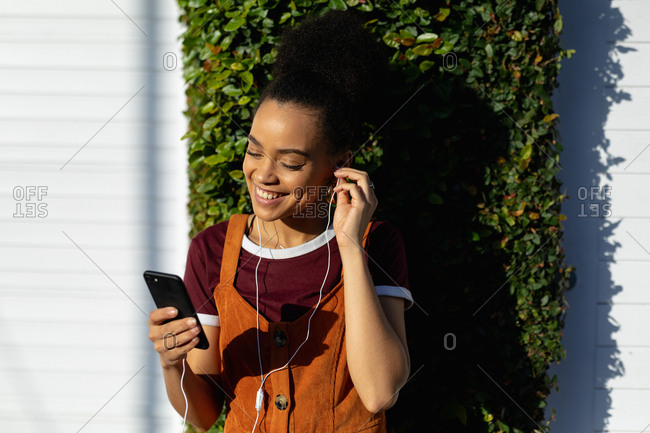 Young woman using smartphone with earphones outdoors