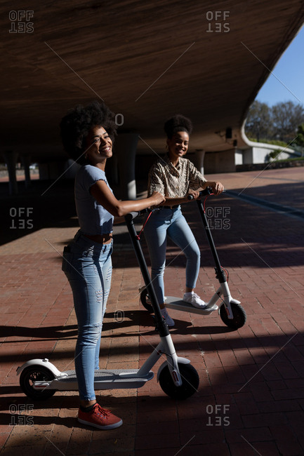 Two young women riding e scooters