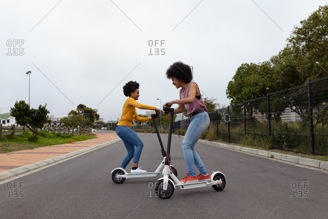 Young women riding e scooters in the street