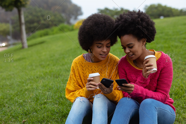 Two young women using smartphones outdoors