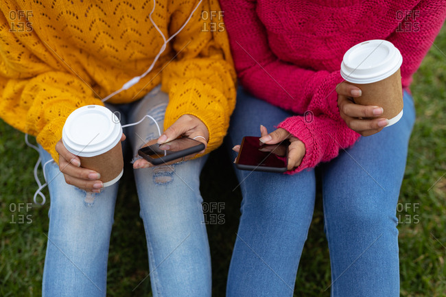 Two young women holding smartphones outdoors