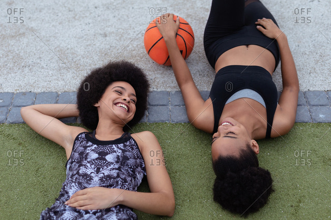 Two young women lying with basketball