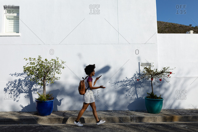 Young woman walking and using smartphone