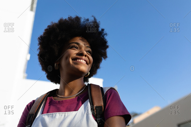Young mixed race woman standing and looking away smiling against blue sky