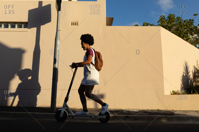 Young woman riding scooter in the street