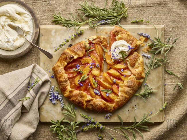 Peach galette on parchment with fresh herbs and mascarpone