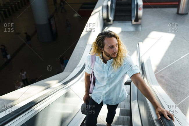 Millennial male with curly long blonde hair on train station escalator