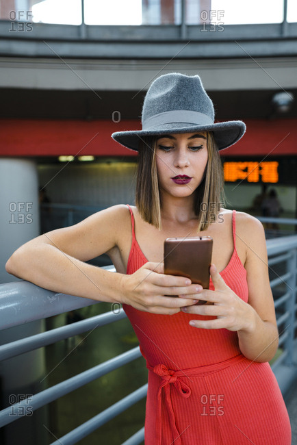 Stylish brunette millennial using smartphone on train station wearing red dress and gray hat