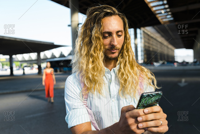 Millennial male with curly long blonde hair texting on phone and carrying a pink backpack outside train station