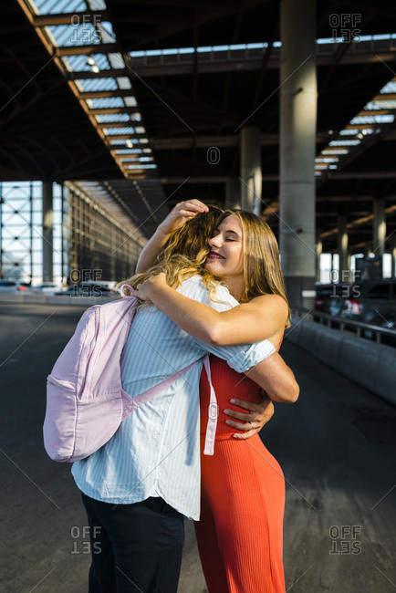 Millennial young woman hugging outside train station to her long curly blonde haired boyfriend