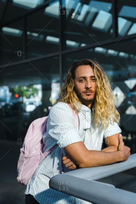 Happy long curly blonde haired guy in casual wear and pink backpack leaning on railing