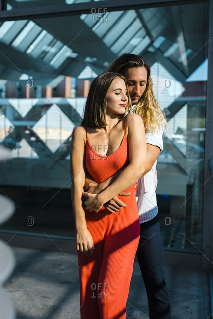 Happy long blonde haired guy embracing attractive young cheerful lady with red dress and looking down