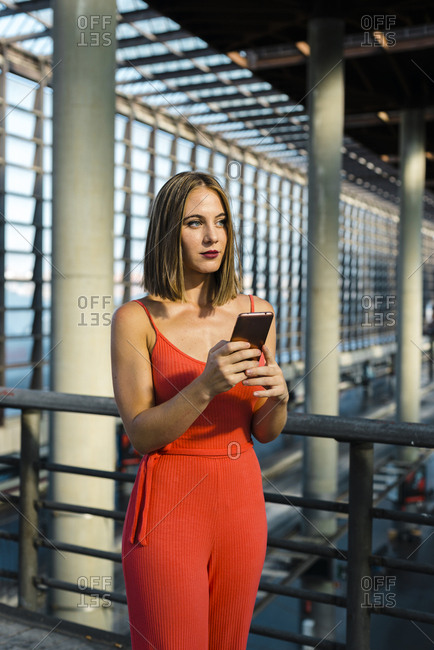 Pensive millennial woman in red dress texting on phone while standing close to train platform