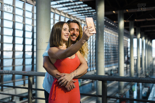 Happy millennial couple taking a selfie with smartphone while standing close to train platform
