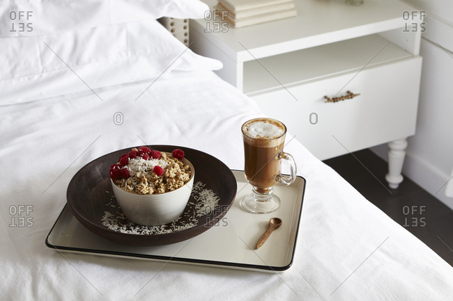 Granola with fresh raspberries and hot cocoa served on a bed