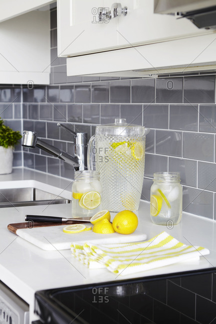 Lemon water on counter in mason jars and a large pitcher