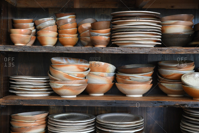 Old plates and bowls stacked on a wooden shelf