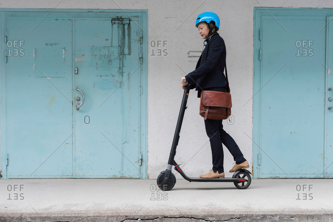 Senior woman riding electric scooter past blue doors, Kuopio, Finland