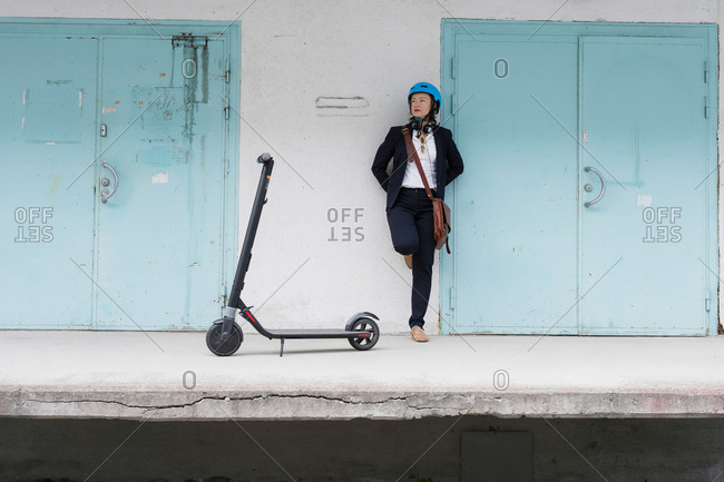 Senior woman standing by blue doors and an electric scooter, Kuopio, Finland