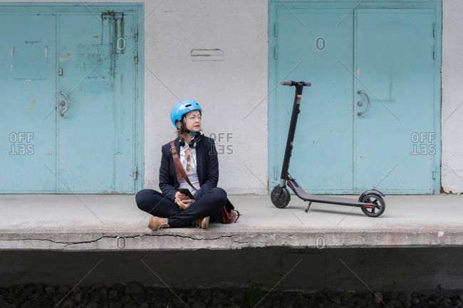 Senior woman sitting on platform by an electric scooter, Kuopio, Finland