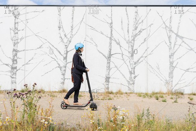 Senior woman riding electric scooter past wall with image of trees, Kuopio, Finland