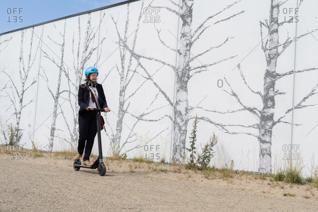 Senior woman riding electric scooter by a wall with image of trees, Kuopio, Finland