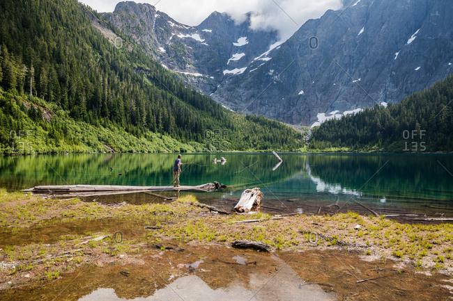 Man fly fishing a mountainside lake