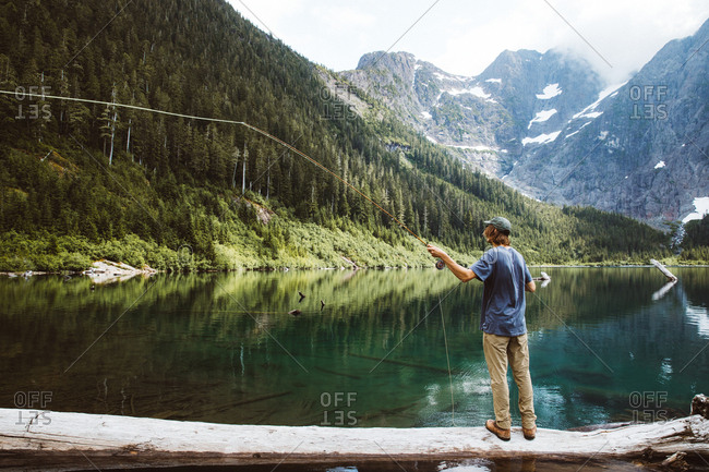 Man standing on fallen tree while fly fishing a mountainside lake