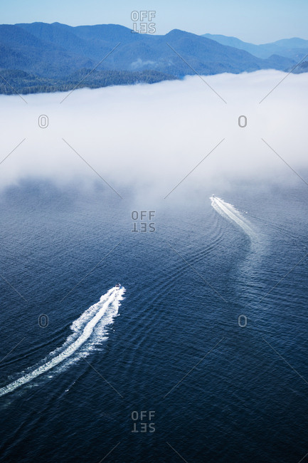 Aerial view of boats in the ocean heading into dense for as they approach land