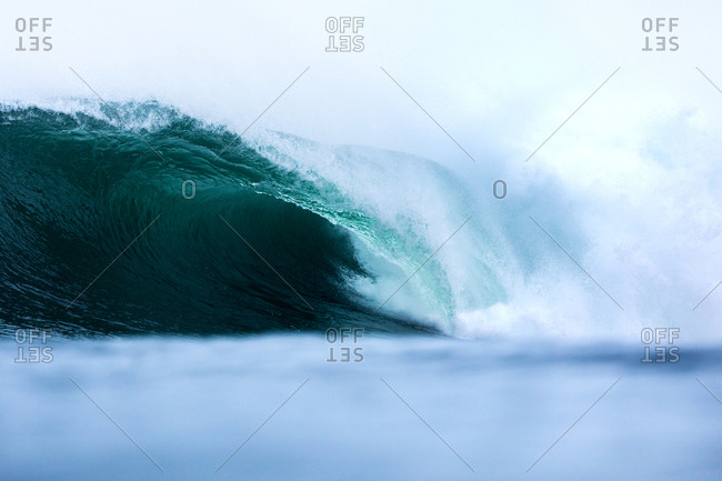 Large turquoise wave rolling in the ocean