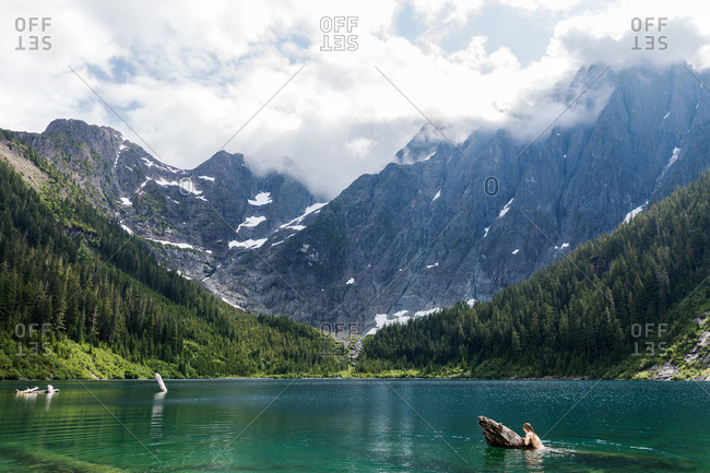 Nude woman swimming in a turquoise lake surrounded by mountains