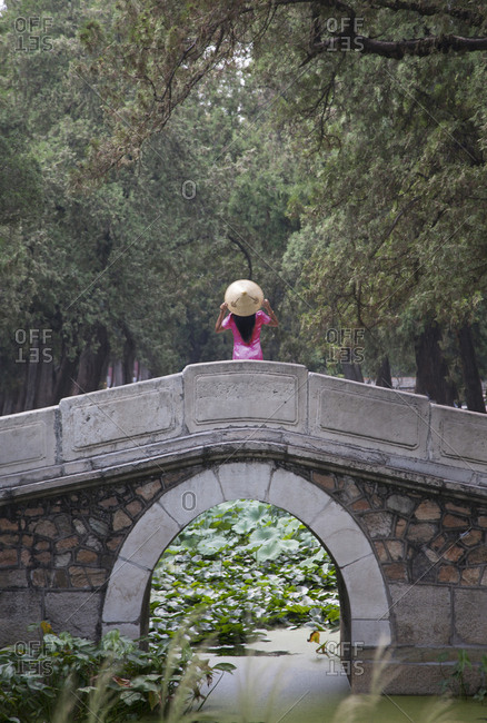 Woman wearing conical hat on arch bridge in Summer Palace gardens, Beijing, China