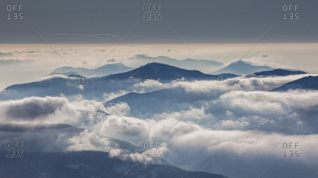Fog over mountain at sunrise in Piedmont, Italy