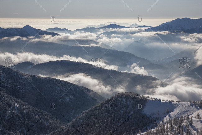 Fog over forest covered mountains in Piedmont, Italy