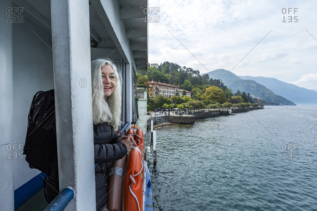 Mature woman smiling on ferry on Lake Como, Italy