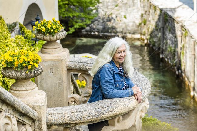 Woman on balcony of Villa del Balbianello by Lake Como, Italy