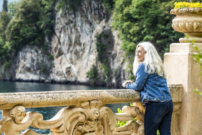 Woman leaning on balustrade at Villa del Balbianello by Lake Como, Italy