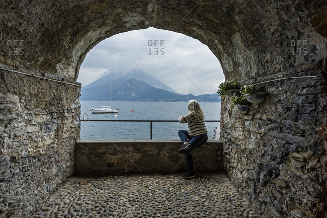 Woman sitting under arch by Lake Como, Italy