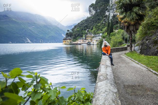 Woman on waterfront in Riva del Garda, Italy