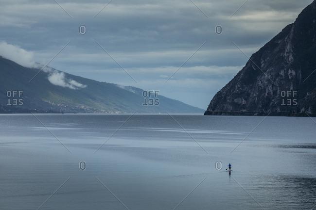 Man paddle boarding on Lake Garda, Italy