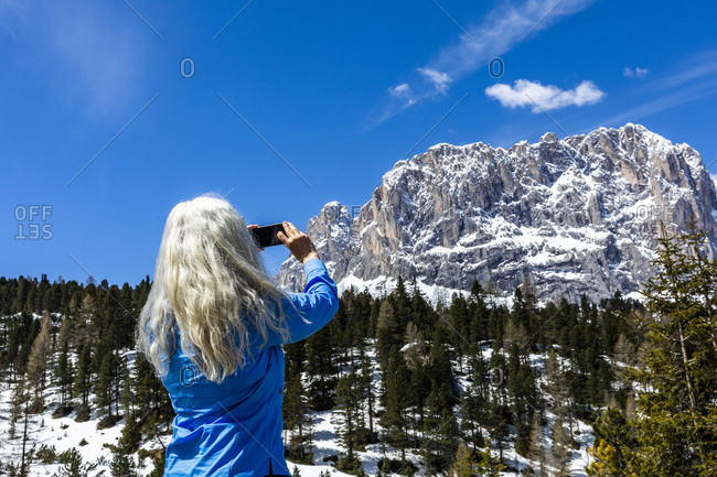 Woman taking photograph with smart phone by mountain in Dolomites, Italy