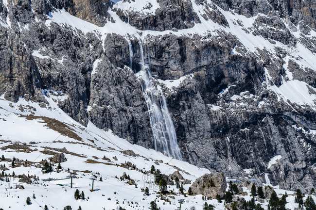 Snow falling down mountain cliff in Dolomites, Italy