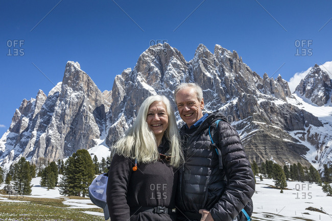 Smiling couple by mountain in Dolomites, Italy